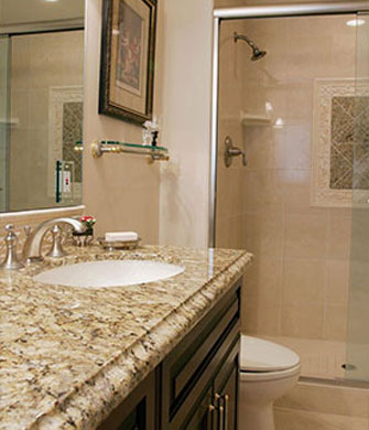 Remodeled bathroom with granite countertops and tiled shower