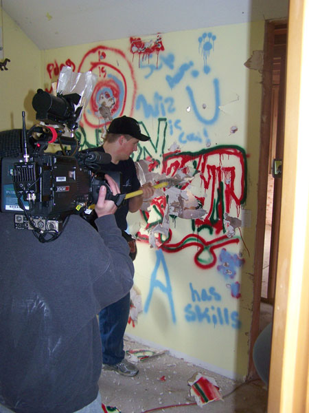 Photo of construction contractor being filmed as he begins demolition of an interior wall.