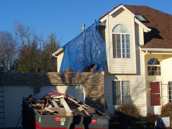 Photo of the exterior of the house with work starting to frame the addition