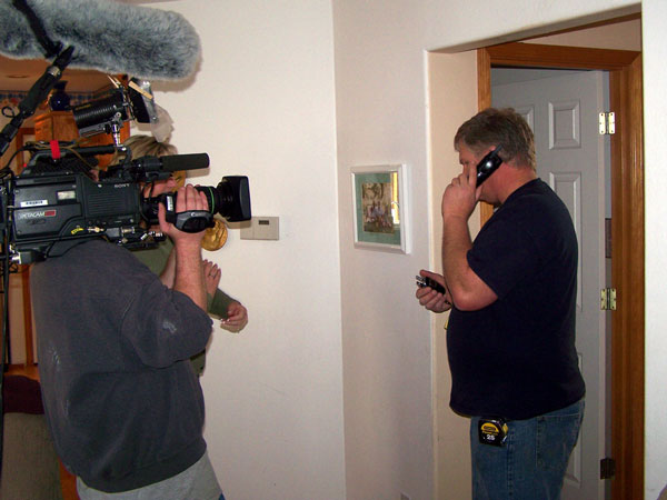 Photo of John Sramek being filmed as he calls a subcontractor