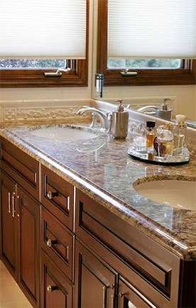 Double bathroom sinks with granite countertops and dark wood cabinetry