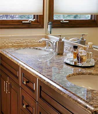 Close up of double sink with granite counter and dark wood cabinets