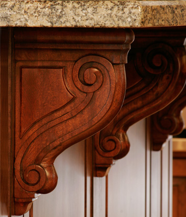 Close up of cherry wood corbels under counter tops in remodeled kitchen