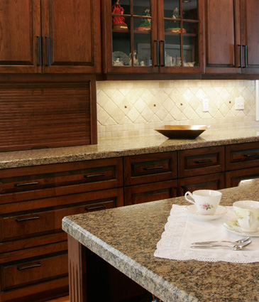Chery wood cabinets, granite counter top, and tumbled tile backsplash in remodeled kitchen