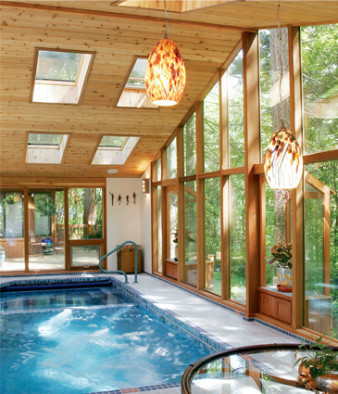 Photo of pool room with cedar framed glass wals and tiled pool, sunlights, and TV nook