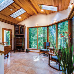 Large room with skylights and big windows that look out to forested area
