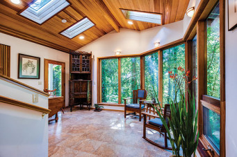 Interior of remodeled home showing wrap-around wall of windows, granite floors, and cedar ceiling with skylights
