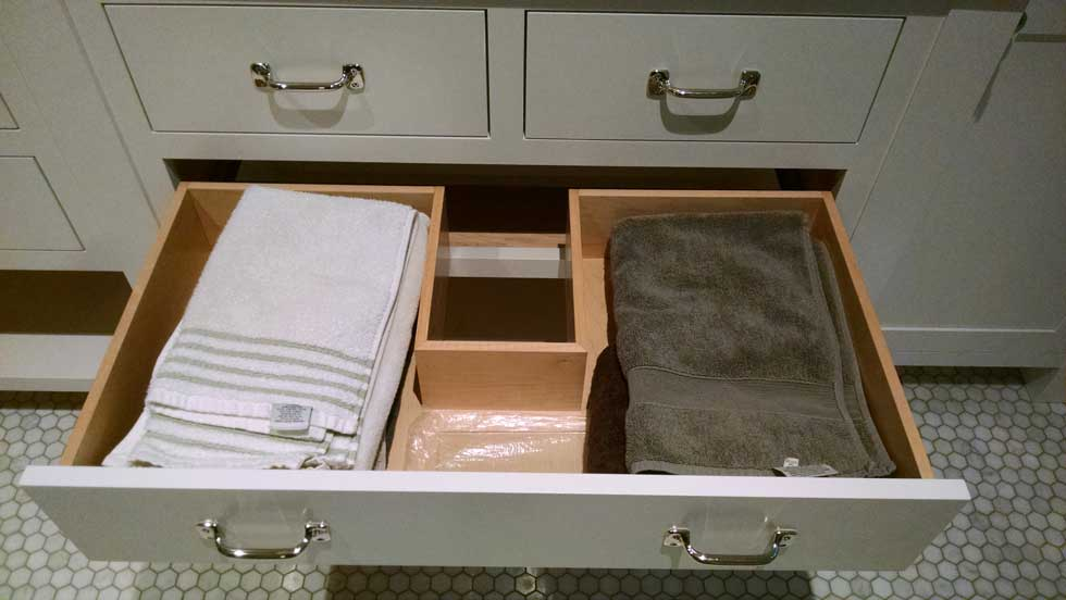 Open drawer in white bathroom cabinets
