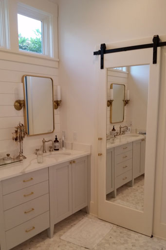 White farm style bathroom vanity with double sinks and mirrors