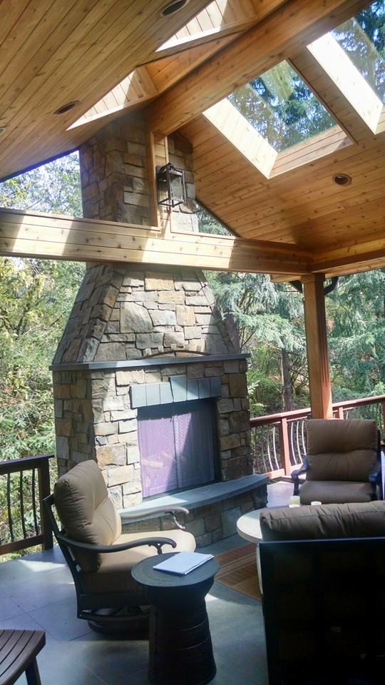 Large outdoor fireplace at the edge of covered deck